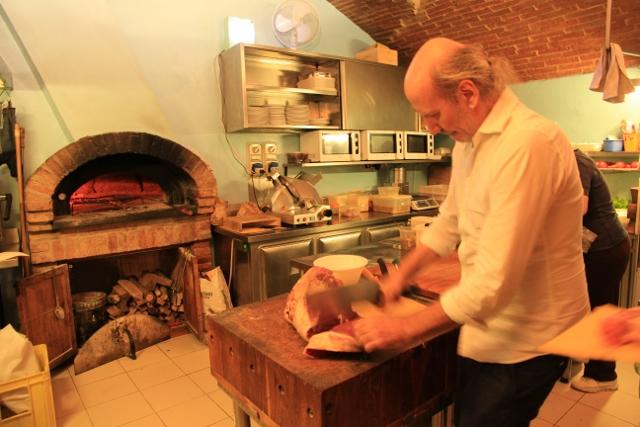 The proprietor of Osteria Acquacheta chops up bistecca fiorentina.